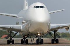 乘出租车在登陆以后的白色波音747飞机 免版税库存图片