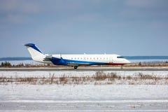 乘出租车在跑道的公司飞机在一个冷的冬天机场 免版税库存图片