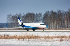 乘出租车在跑道的私人飞机在一个冷的冬天机场 免版税库存图片