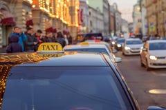 乘出租车对城市的中心在一条拥挤的街上的有繁忙运输的和反映在玻璃晚上光  免版税图库摄影