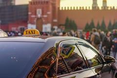 乘出租车对城市的中心在一条拥挤的街上的有许多人民的和反映在大都会玻璃晚上光  库存图片