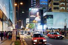 乘出租车并且阐明了在夜城市香港街道上的标志  免版税库存照片
