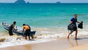 乘出租车有地方oprators的小船与热带海滩的游人 免版税库存照片