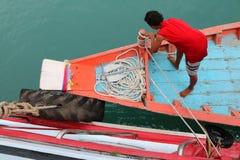 乘员组使用一条绳索被栓入有一条大小船的一条小船 免版税库存照片