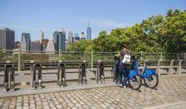 乘在曼哈顿地平线前面的妇女一辆自行车在纽约 免版税库存照片