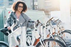 乘在自行车的美国黑人的妇女一辆自行车分享平台 库存图片