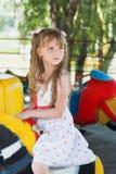 乘坐一个五颜六色的转盘的逗人喜爱的小小女孩 免版税图库摄影