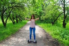 乘坐一个电子滑行车户外-翱翔板,巧妙的摆轮,电罗经滑行车, hyroscooter,个人Eco运输的妇女 免版税库存照片