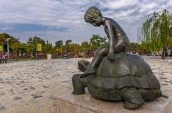 乘坐一只巨大的乌龟的孩子 免版税库存照片