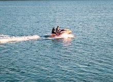 乘坐一艘汽艇的人们在镇静海洋 免版税图库摄影