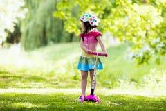 乘坐一辆五颜六色的滑行车的小女孩 库存图片