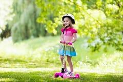 乘坐一辆五颜六色的滑行车的小女孩 免版税库存图片
