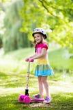乘坐一辆五颜六色的滑行车的小女孩 免版税库存照片