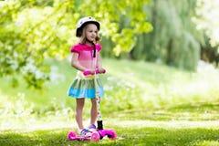 乘坐一辆五颜六色的滑行车的小女孩 库存照片