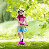 乘坐一辆五颜六色的滑行车的小女孩 图库摄影