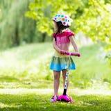 乘坐一辆五颜六色的滑行车的小女孩 免版税图库摄影