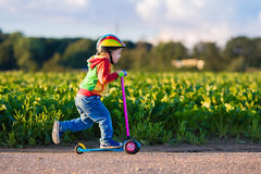 乘坐一辆五颜六色的滑行车的小男孩 免版税库存图片