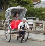 乘坐一辆人力车的游人在京都,日本 免版税库存照片