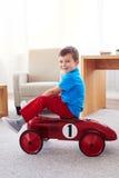 乘坐一辆减速火箭的玩具汽车的小男孩 免版税库存照片