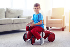 乘坐一辆减速火箭的玩具汽车的英俊的小男孩 库存照片