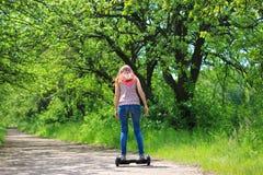 乘坐一辆电子滑行车的妇女户外 图库摄影