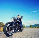 乘坐一辆自定义的摩托车的骑自行车的人在一条开放路 库存照片