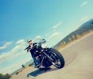 乘坐一辆自定义的摩托车的骑自行车的人 免版税库存图片
