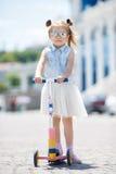 乘坐一辆滑行车的小女孩在城市 免版税库存照片