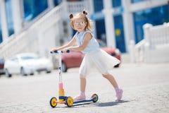 乘坐一辆滑行车的小女孩在城市 免版税图库摄影