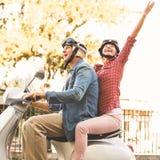 乘坐一辆滑行车的愉快的成熟夫妇在城市 免版税库存照片