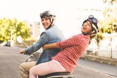 乘坐一辆滑行车的愉快的成熟夫妇在城市 免版税图库摄影
