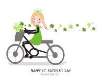 乘坐一bicyle的逗人喜爱的女孩与愉快的圣帕特里克的天 免版税图库摄影