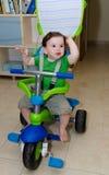 乘坐三轮车的逗人喜爱的婴孩 免版税库存图片