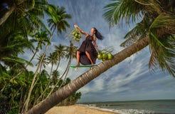 乘坐下来用椰子的妇女 图库摄影