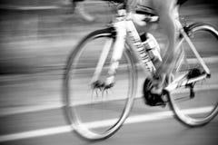 乘坐与乘坐在路的自行车骑士的行动的骑自行车者 免版税库存照片