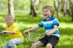 乘坐他们的自行车的小孩儿 免版税库存图片