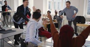 乘坐优胜者办公室椅子庆祝成功的愉快的女性经理与不同种族的同事一起在现代办公室 影视素材