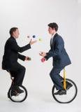 乘坐单轮脚踏车的玩杂耍的生意人 免版税库存照片