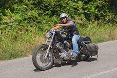 乘坐哈利戴维森Sportster的骑自行车的人 免版税库存图片