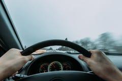 乘坐在一辆汽车的轮子后在冬天 免版税库存图片