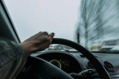 乘坐在一辆汽车的轮子后在冬天 图库摄影