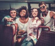 乘坐在一辆观光的公共汽车的朋友 免版税库存图片