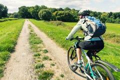 乘坐在乡下公路的妇女自行车骑士 免版税库存照片