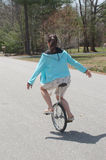 乘坐在住宅邻里街道下的年轻少年妇女平衡在单轮脚踏车 免版税库存图片