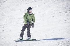乘坐在修饰的雪小山下的男性成人挡雪板 免版税库存图片