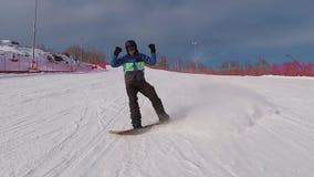 乘坐在倾斜的挡雪板在山 在滑雪服打扮的年轻人是高兴的他安排井滚动 股票视频