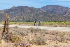 乘坐在南部非洲的干旱台地高原的一条土路的两个骑自行车者 免版税库存照片
