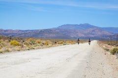 乘坐在南部非洲的干旱台地高原的一条土路的两个骑自行车者 库存图片