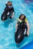 乘坐在后院水池的两个男孩浮游物 免版税库存图片