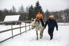 乘坐在哥萨克人的复兴节目的框架里孩子训练在列宁格勒地区 免版税库存照片